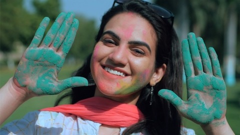 Excited young woman showing colorful hands during colorful Holi celebrations