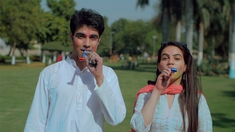 Excited couple blowing party whistle while celebrating Holi festival in a garden