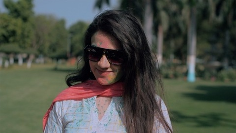 Charming girl wearing sunglasses enjoying Holi party on a bright sunny morning