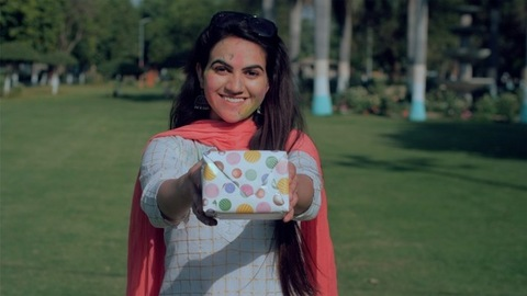 Lovely girl smeared with Gulal holding a colorful gift during Holi celebration