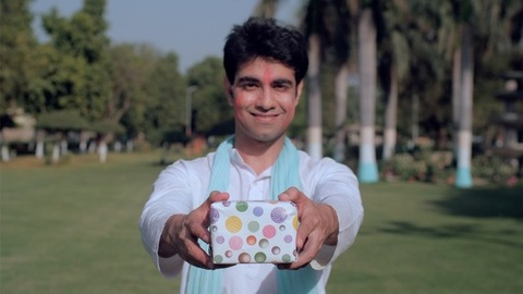 Cheerful man greeting people with a colorful present during Holi celebration