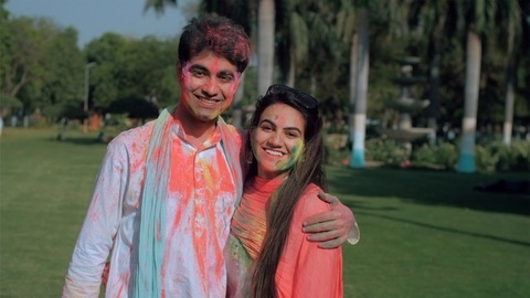 Cute Indian couple applying Gulal on each others face while celebrating Holi