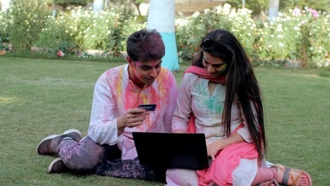 Friends making an online transaction using a bank card and laptop during Holi