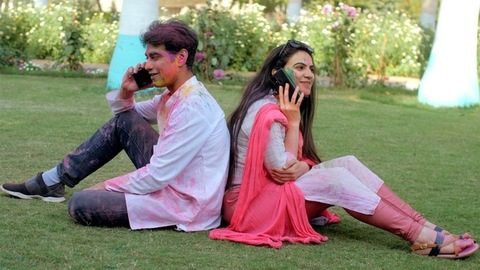 Two youngsters talking on their mobiles with their backs against each other - Holi Day