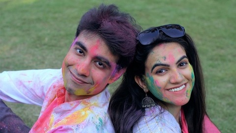 Carefree urban friends relaxing in the garden after celebrating the Holi festival