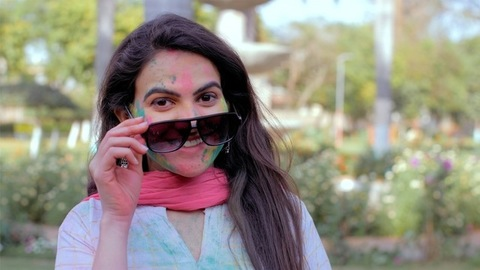Indian lady with Gulal on the face with sunglasses during outdoor holi party
