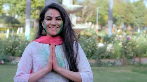 Traditional Hindu girl joining her hands in Namaste gesture to greet on Holi