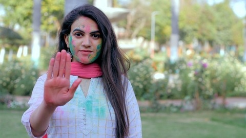 Bold urban girl showing stop sign with hands during Holi festival celebration