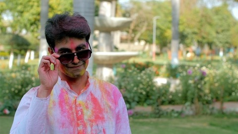 Man smeared with Holi colors with sunglasses and winking at the camera