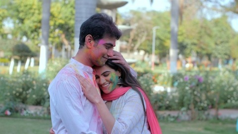 Young Indian couple with multicolor Gulal on face hugging each other in a park during Holi party