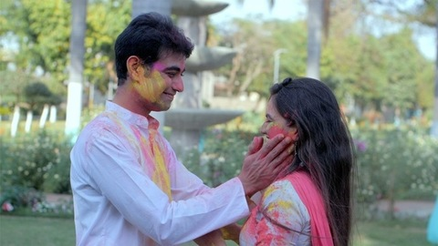 Happy couple applying Gulal on each other during traditional Holi celebration