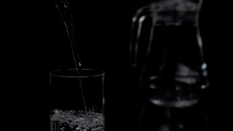 Pure water pouring in a transparent glass with bubbles forming - refreshing to drink