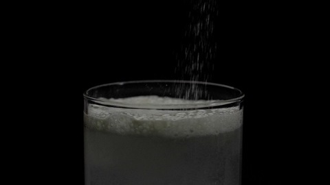Fruit salt antacid dissolving in a transparent glass of water - healthcare and medical