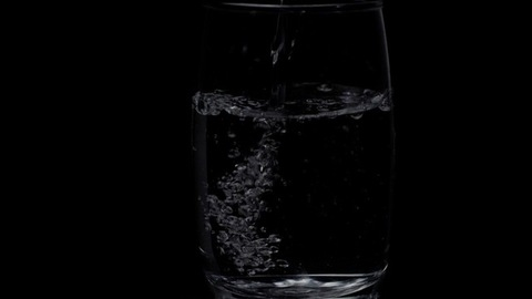 More water is added / pouring to an already filled glass of water - hygienic drink