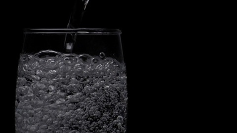 Aerated beverage / soda tonic water pouring / poured in a clear glass