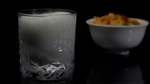 Fizzy medicine / soda  being put in a transparent glass of water kept on a table