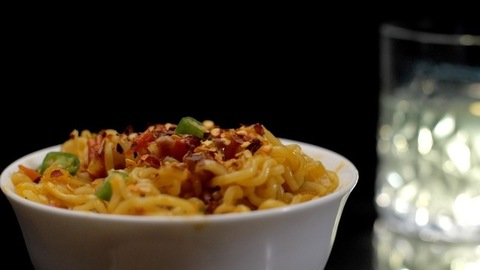 Hot and spicy instant noodles kept in a ceramic bowl on a wooden surface