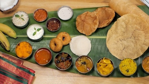 Different varieties of tasty South Indian food being served on a banana leaf