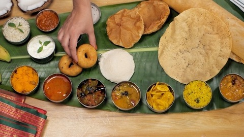 Female hands keeping a Medu Vada with a variety of food on a banana leaf
