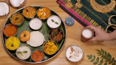 Female hands keeping a glass of buttermilk (Chaas) near a South Indian Thali