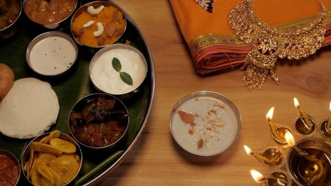 Traditional Saree, jewelry, and metal oil lamp decorated near a vegetarian Thali