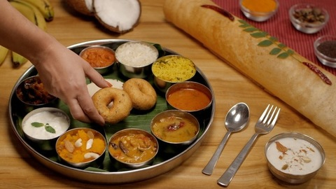 Female hand placing a Medu Vada with other south Indian foods on a plate