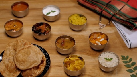 A plate of Poori with different south Indian curries and sweets placed on a table
