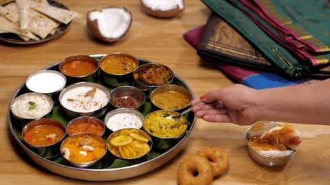 Female hands taking a bite of lemon rice from a South Indian vegetarian Thali