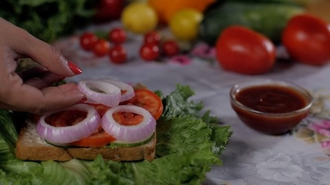 Indian cook's hand keeping round-shaped onion rings inside an open vegetarian sandwich