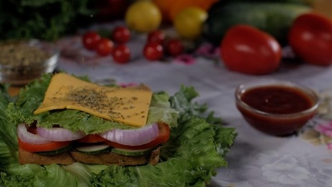Flavorful oregano falling on a cheese slice used to prepare a delicious sandwich