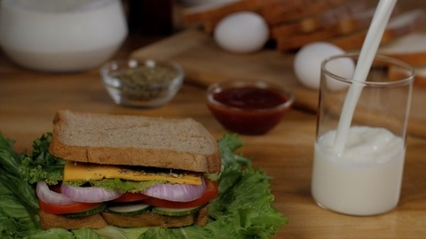Pure milk is poured into a clear glass to be served with a healthy vegetarian sandwich