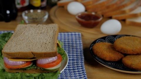 Slice of brown bread falling on cheese vegetable sandwich - tasty morning breakfast