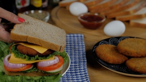 Female hands keeping a slice of brown bread on a tasty vegetarian sandwich