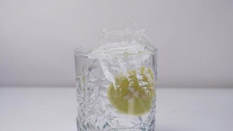 Lemon slice splashing in cold water - cool refreshing summer drinks