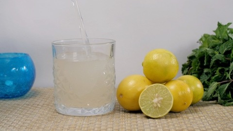 Water falling inside a glass half-filled with a refreshing lemon juice