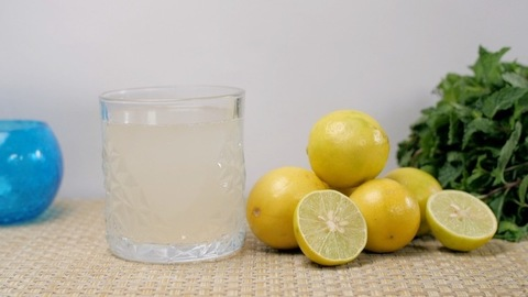 Tasty and healthy lime water flavored with mint leaves in a transparent glass