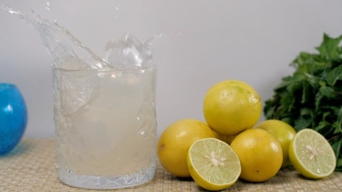 Big ice cubes dropping in a glass of citrus refreshing lemonade placed on a table