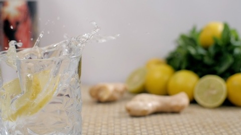 Lemon slices falling in refreshing soda tonic water inside a transparent glass