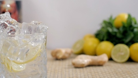 Big ice cubes falling in a glass of fresh soda / tonic water with lemon slices