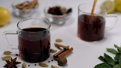Aromatic black spicy tea falling in a transparent cup - traditional Indian beverage