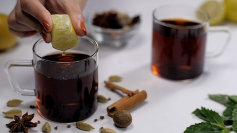 Hands squeezing fresh lime juice in a cup of spicy black tea - Indian drink
