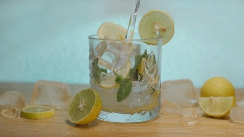 Fresh lemon juice pouring in a transparent glass decorated with a slice of lemon