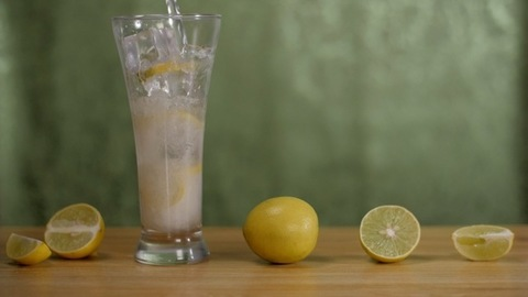 Fresh lemon juice is poured into a transparent glass with ice cubes