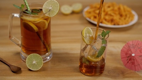 Pouring of lemon-flavored ice tea in transparent glass - cool summer drink