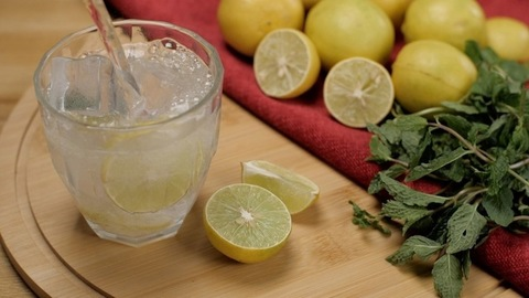 Healthy iced lemon drink with mint leaves for detoxification poured in a glass