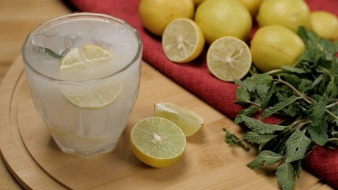 Bubbling soda infused lemonade with big ice cubes and a lemon slice in a glass