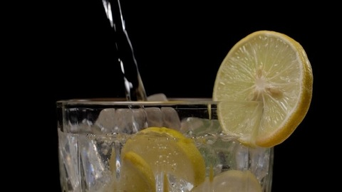 Pouring of healthy fresh lime squash with big chunks of ice in a clear glass