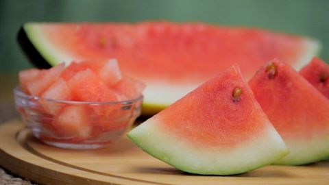 Pan shot of juicy sliced watermelon with brown seeds kept together on a wooden surface