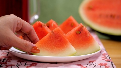 Female hands taking a piece of juicy watermelon from a ceramic plate - Summer fruit India