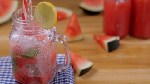 Soda water falling in a glass jar filled with pieces of watermelon, ice, and mint - Summer fruit India